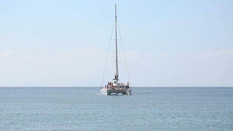 Trimaran full of tourists eager to see sights approaching rocky island shore Footage