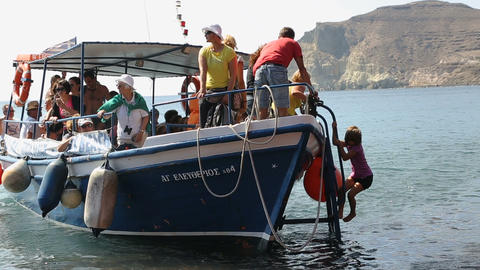 Pleased with sea excursion tourists going down from boat to shore of red beach Footage
