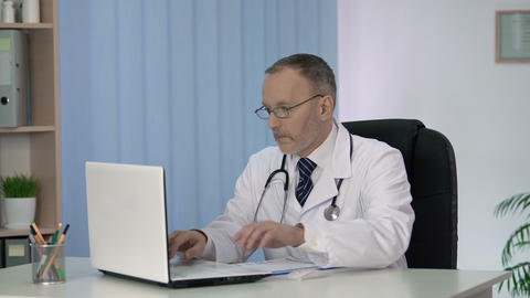 General practitioner putting patient data in electronic medical record on laptop Archivo