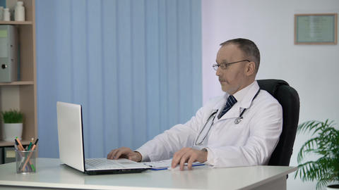 Doctor studying treatment methods on laptop, surprising by innovative approach Footage