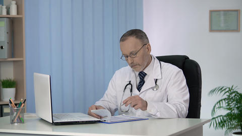Head of therapeutic department finishing his workday, filling in medical forms Footage