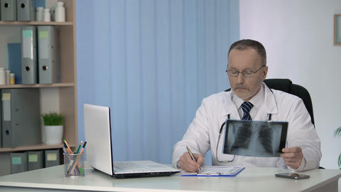 Pulmonologist examining and describing patient lungs x-ray scan before surgery Footage