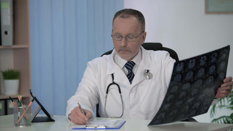 Experienced neurologist carefully examining brain MRI, making notes in form Footage