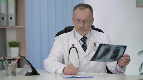 General practitioner examining x-ray, filling medical form for hospitalization Footage