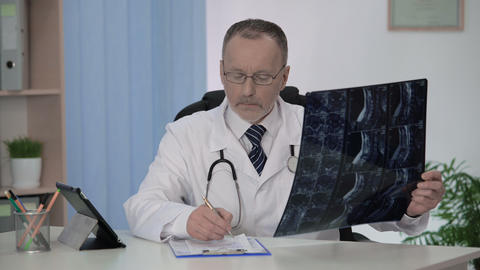Spinal surgeon examining backbone mri, making notes in patient's medical card Footage