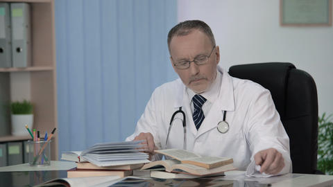 Physician reading medical books looking for information about rare diseases Footage