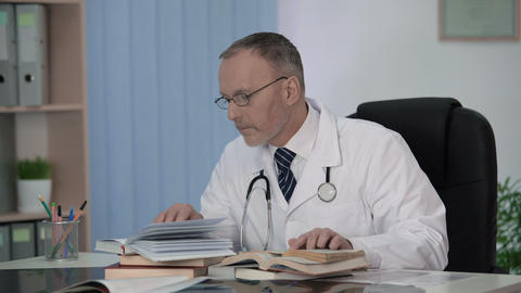 Doctor examining medical science literature to diagnose seriously ill patient Footage