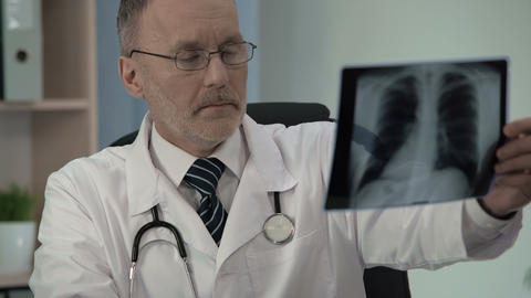 Male pulmonologist attentively scrutinizing chest x-ray, looking for pathology Footage