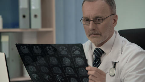 Neurologist checking MRI image, confirms pathology in patients cerebral cortex Live Action