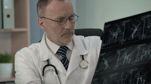 Neurologist examining patient venogram and typing his findings in patient card Live Action