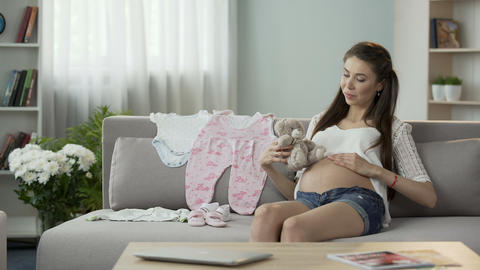 Pregnant female holding teddy bear close to belly, rubbing it gently, baby toys Footage