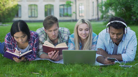 Multi-ethnic men and women doing homework on grass on campus, higher education Footage