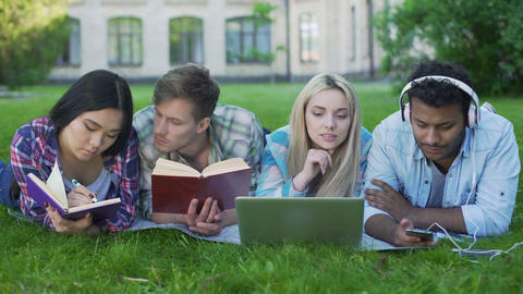 Group of friends lying on lawn on campus and preparing for test, student's life ビデオ