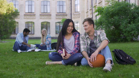 Student couple sitting on grass near college, talking and smiling, first love Footage