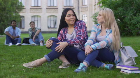 Females sitting on grass, talking and smiling, guys looking at girls, flirt Live Action