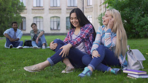 Girls students looking at guys and flirting, teens sitting on lawn near college Live Action
