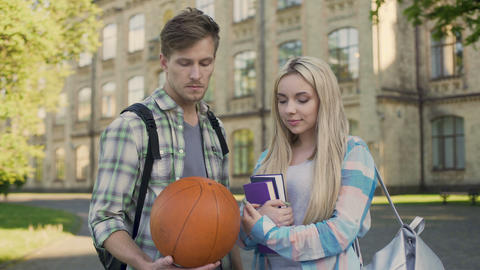 Student holding ball, flirting with pretty girl near university, asking for date Live Action