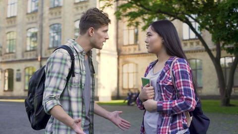 Emotional male student talking with ex-girlfriend near university, relationship Footage