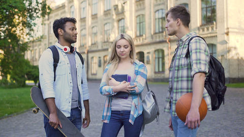 Students standing near college, chatting and flirting. Blonde choosing boyfriend Footage