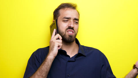 Man in casual blue shirt talks on the phone over an yellow background ビデオ