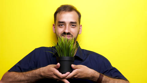 Man smiling to the camera and showing a pot with green grass ビデオ