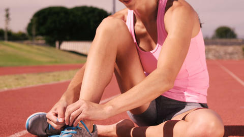 Sportswoman tying up her shoelaces while sitting Footage