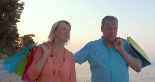 Mature couple relaxing with seaside walk after shopping Footage