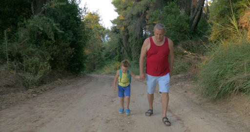 Man and Boy Hiking along the Country Road Footage