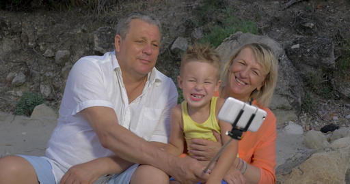 Grandparents and grandchild making funny mobile selfie Footage