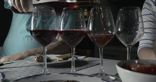 Man pouring red wine in four glasses Footage