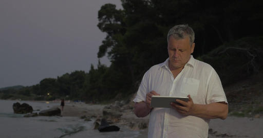 Senior man using tablet PC on beach in late evening Footage