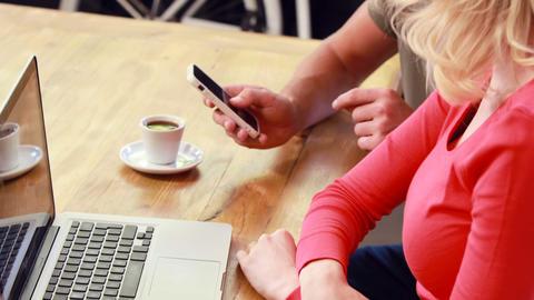Boyfriend showing smartphone to girlfriend Footage