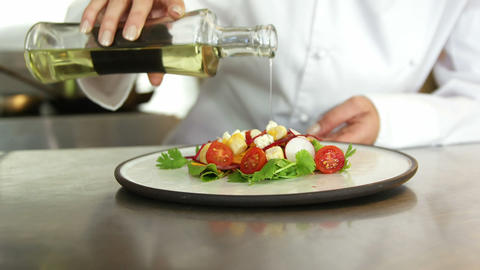 Chef pouring salad dressing over a salad Live Action
