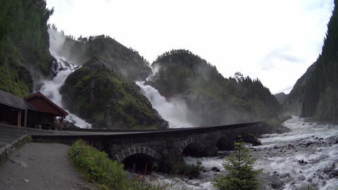 Large cascade waterfall. Road in Norway passing over the waterfall Live Action