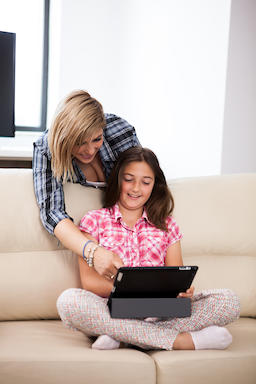 Mother showing her cute teenage daughter something on the tablet PC フォト