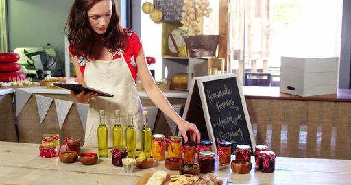 Female staff arranging olives, preserves and olive oil on counter Live Action