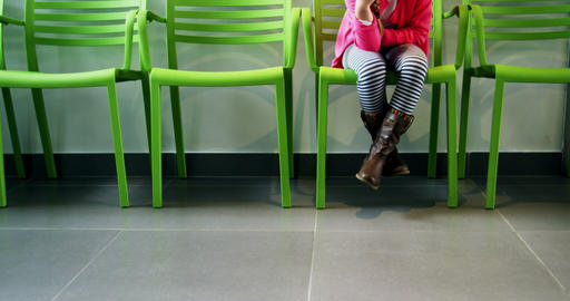 Upset girl sitting on chair in hospital corridor Footage