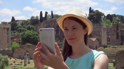 Woman near Forum Romanum doing selfie on mobile phone. Tourist taking photo ビデオ