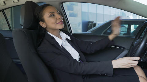 Mixed-race female in car, looking in rear-view mirror and trying driver seat Footage