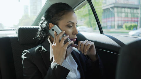 Woman in business suit on back seat of car, having conversation on phone, stress Footage