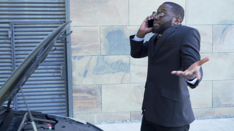 Male in suit arguing over cellphone standing by broken car with open hood, hurry Footage