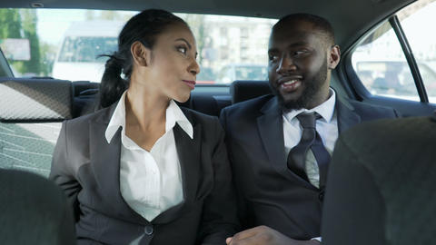 Man and woman in business suits sitting at back seat of car, flirting, affection Live Action
