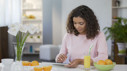 Mixed race young woman reading article on tablet, body care and nutrition Footage