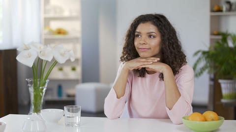 Beautiful mixed race woman sitting at table and daydreaming, future plans Footage