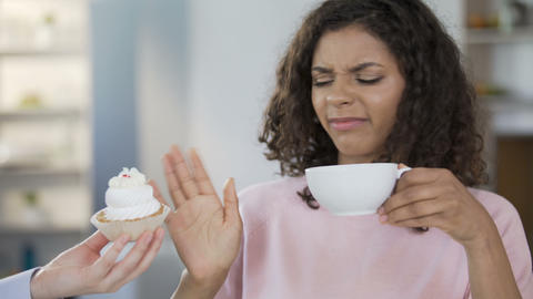 Attractive young woman drinking tea, saying no to cream-cake, healthy dieting Footage