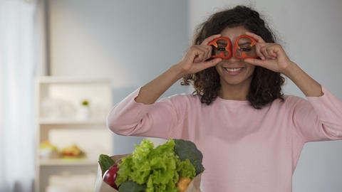 Beautiful woman bringing pepper rings to eyes, smiling, healthy eating habits Live Action