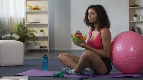 Mixed race woman sitting on floor in sportswear and eating salad, body care Live Action