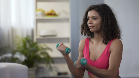 Young woman lifting dumbbells alternately, exercising, body care, weight control Live Action