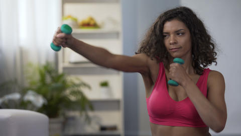 Sporty girl doing boxing movements with dumbbells in hands, workout, fitness Live Action