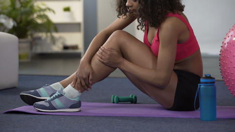 Girl in gym outfit sitting on floor and massaging cramped leg, strained muscle Live Action